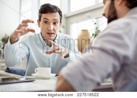 Negotiations. Handsome Serious Dark-eyed Man Talking With His Partner Sitting Next To Him And Drinki