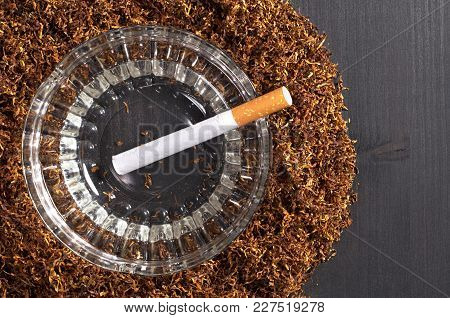 Cigarette In Glass Ashtray And Tobacco On A Black Wooden Background, Top View