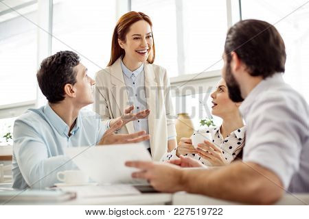 Hey Guys. Beautiful Alert Red-haired Young Woman Smiling And Talking With Her Co-workers Sitting At