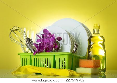 On Drying Rack Clean Dishes, Utensils, Glove, Sponge And Flowers Orchid On Yellow Background