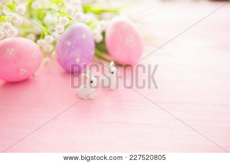 Colorful Easter Egg With Rabbits Toy Against A Pink Wood Background.