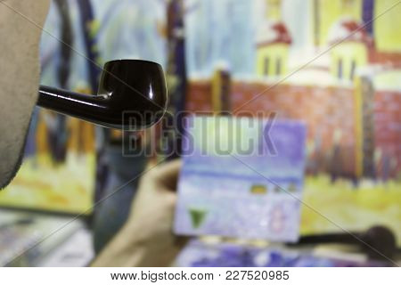 Artist At Work, Painting Oil Painting In The Studio And Smoking Pipe. Closeup With Pipe