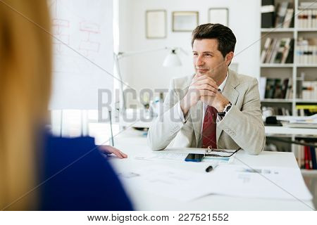 Company Director Sitting At Table Thinking About Future Plans