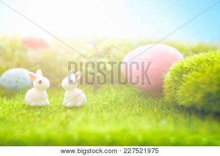 Spring Meadow With Miniature Easter Rabbits And Easter Eggs.
