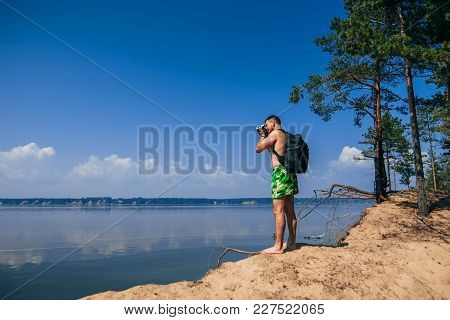 Traveler Photographer With Backpack Taking Pictures Of Summer On The Beach From Behind