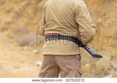 Close Up Picture Of Hunter With Bandolier Full Of Ammo For Shotgun