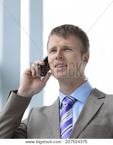 Businessman at the window talking on the phone