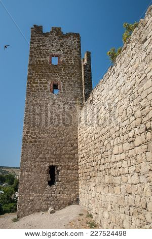 Stone Tower Of An Ancient Fortress With Adjoining Rocky Walls On Blue Sky Background