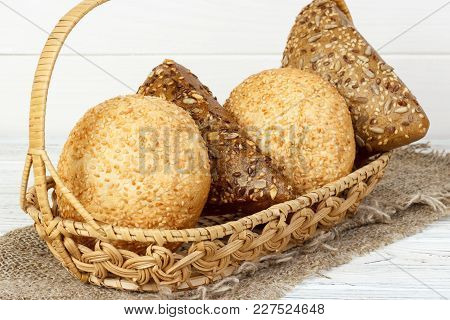 Bread Buns In Wooden Basket On White Wooden Background.