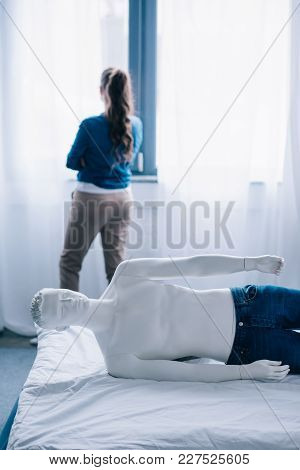 Back View Of Woman Standing At Window And Layman Doll Lying On Bed, Loneliness Concept