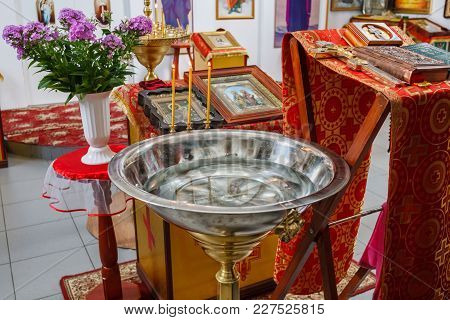 The Baptismal Font With Candles And A Table With Icons And A Cross In The Church.