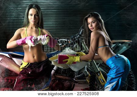 Two Sexy Young Female Models Washing Motorcycle