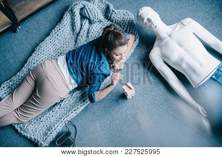 Overhead View Of Woman Playing Blocks Wood Game With Layman Doll Near By At Home, Perfect Relationsh
