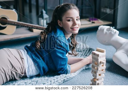 Beautiful Woman Lying Near Mannequin And Blocks Wood Game On Floor At Home, Loneliness Concept