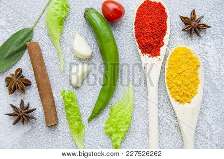 Dry Spices And Herbs In Wooden Spoons With Fresh Herb Springs, Cherry Tomatoes, Cinnamon And Garlic