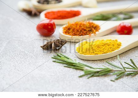 Dry Spices And Herbs In Wooden Spoons With Fresh Herb Springs On A Light Stone Background With Copy