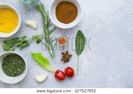 Dry Spices And Herbs Ceramic Bowls, Fresh Cherry Tomatoes, Herbs And Garlic Cloves On A Light Stone