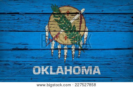 Oklahoma State Grunge Wood Background With Flag Painted On Aged Wooden Wall.