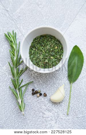 Dry Herbs In A Ceramic Bowl, Fresh Herbs And Garlic Clove On A Light Stone Background With Copy Spac