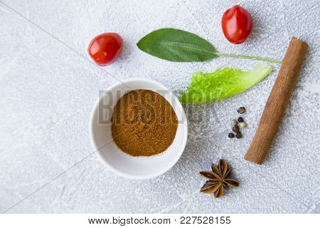 Dry Spices In A Ceramic Bowl, Fresh Acherry Tomatoes, Cinnamon And Herbs On A Light Stone Background