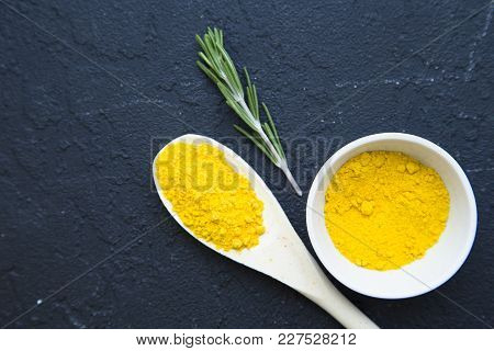 Dry Curry Spices In A Wooden Spoon And Ceramic Bowl, A Sping Of Rosemary On A Black Stone Background