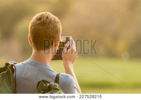 Caucasian Man Taking A Landscape Photo On His Mobile Phone