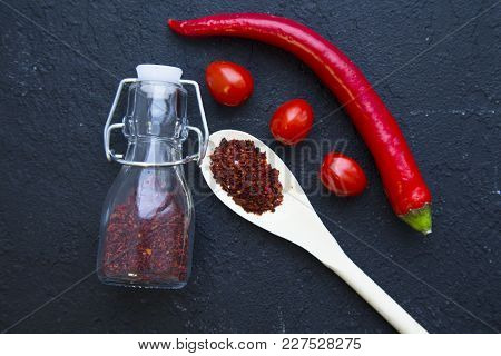 Dry Spices In A Wooden Spoon And Glass Jar , Red Chili Pepper And Cherry Tomatoes On A Black Stone B
