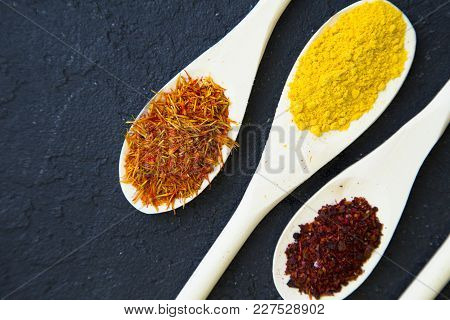Dry Spices And Herbs In Wooden Spoons, Black Stone Background With Copy Space, Top View