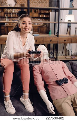 Woman With Manikin Near By Playing Video Game At Home, Loneliness Concept
