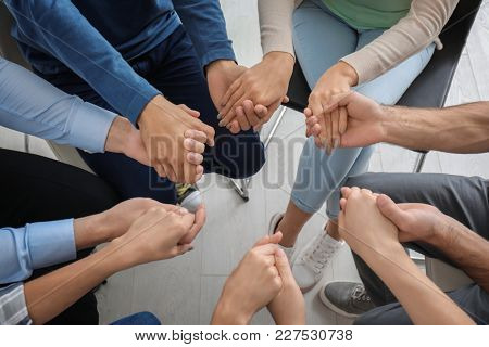 Hands of people supporting each other at group psychotherapy session