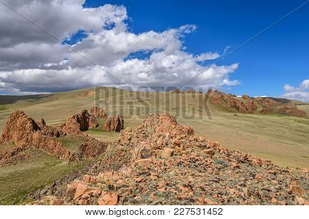 Remains Of An Ancient Ruined Fortress In The Steppe In The Mountains On The Background Of The Blue S