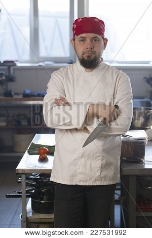 Portrait Of A Fashionable Chef In Bandana Holding A Knife In A Kitchen, Concept Of Cooking And Haute