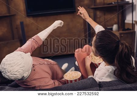 Rear View Of Woman Eating Popcorn While Watching Film Together With Manikin At Home, Perfect Relatio