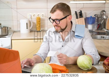 Man Sitting At Kitchen Table In Front Of Open Laptop, Concentrated On Paperwork, Paying Domestic Bil