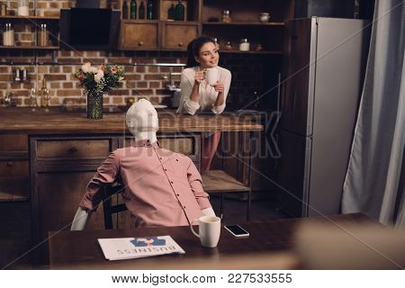 Selective Focus Of Young Woman With Cup Of Coffee And Manikin At Table In Kitchen, Perfect Relations