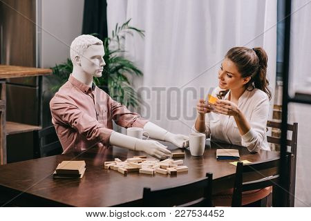 Young Woman Playing Game Together With Layman Doll At Table With Cups Of Coffee, Loneliness Concept