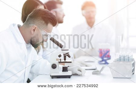 scientist looking in a microscope sitting in the lab.