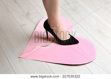 Woman stepping on broken paper heart on floor. Relationship problems