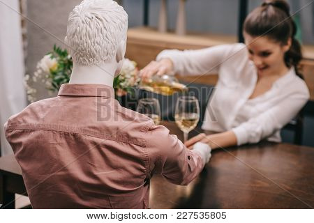 Selective Focus Of Woman Pouring Wine Into Glass While Sitting At Table With Layman Doll, Unrequited