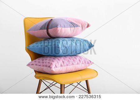 Stack of pillows on chair against white background