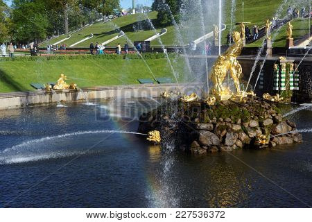 PETERHOF, ST. PETERSBURG, RUSSIA - JUNE 4, 2017: People walking around golden statues of the Grand Cascade. The cascade was built in 1715-1724 and is one of the remarkable fountain constructions