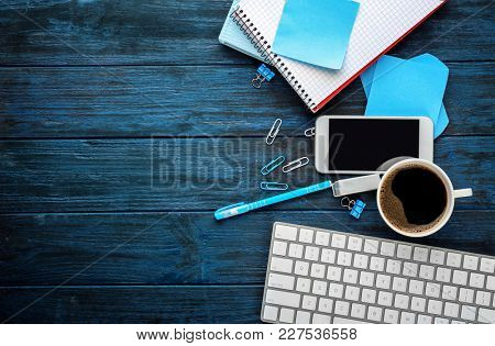 Office stationery with keyboard, cup of coffee and phone on table