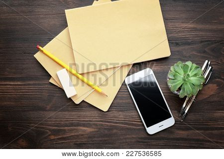 Office stationery and phone on table