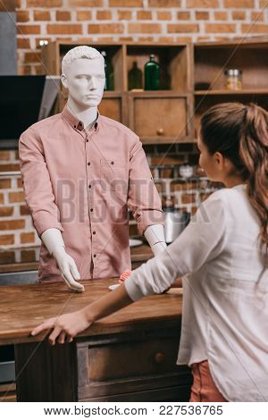 Selective Focus Of Woman Giving Cupcake To Manikin In Casual Clothing, Loneliness Concept
