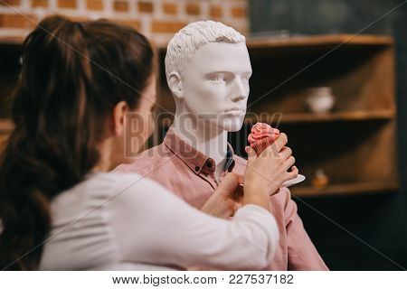 woman pretending to feed mannequin with cupcake at home, perfect relationship dream concept poster