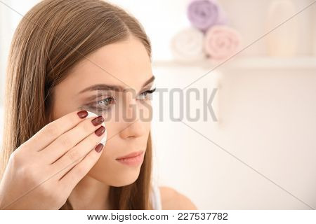 Young woman removing makeup with cotton pad indoors. Eyelash loss problem