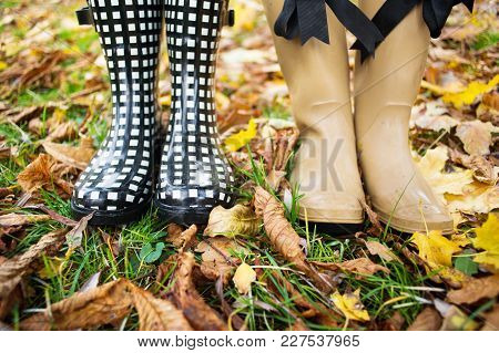 Girl Wearing Rain Boots Standing In A Puddle On Warm Summer Day