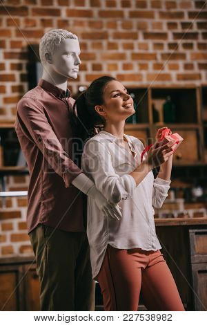 young woman opening gift in hands with manikin hugging her behind, perfect man dream concept poster