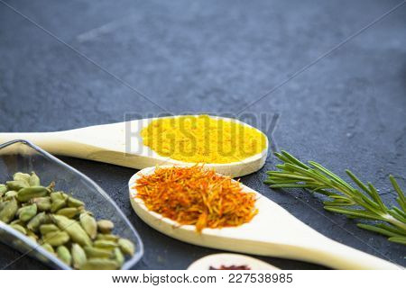 Dry Spices And Herbs In Glass And Wooden Spoons, A Sping Of Rosemary, Black Stone Background With Co