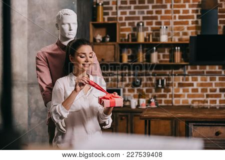 Young Woman Opening Gift In Hands With Manikkin Hugging Her Behind, Perfect Man Dream Concept